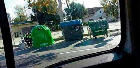 Agentes escondidos tras un contenedor basura